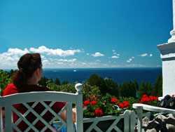 A woman enjoying the view from the porch of the Grand Hotel on Mackinac Island Michigan.